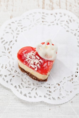 A heart-shaped cake with cream filling and a red jelly topping