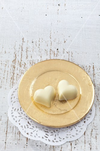 Two white chocolate hearts on a golden plate