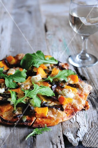 A pizza topped with pumpkin, biltong and rocket
