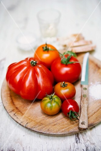 Various tomatoes on a round wooden board