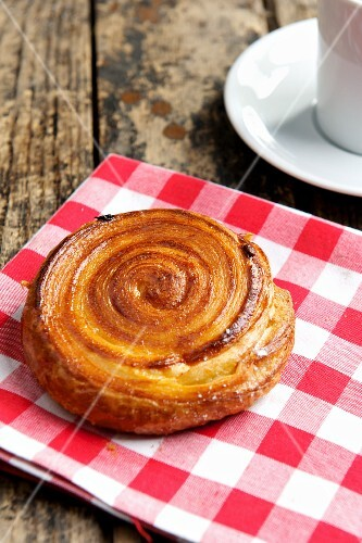 A puff pastry spiral on a checked cloth