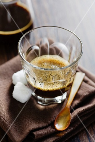A glass of espresso with sugar cubes