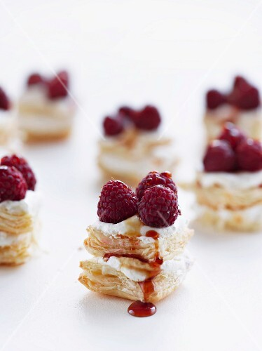 Bite-sized puff pastries with cream, caramel and raspberries