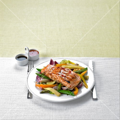 Marinated, grilled salmon on a bed of stir-fried vegetables