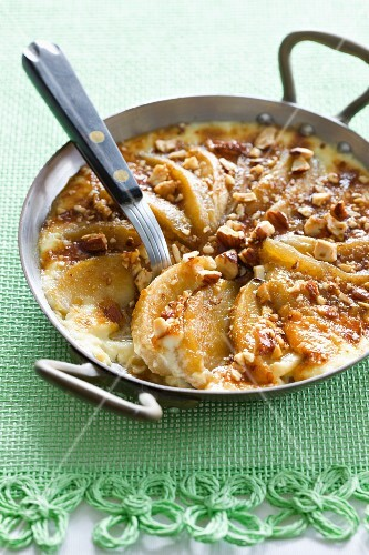 Apple gratin with calvados and hazelnuts in a pan