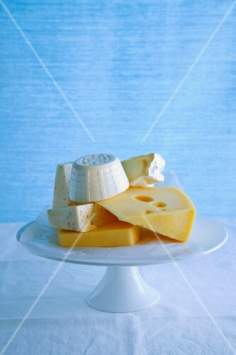 Various types of cheese on a cake stand