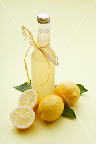A bottle of lemonade and fresh lemons
