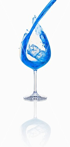 A blue cocktail being poured into a glass with ice cubes