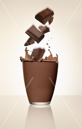 Pieces of chocolate falling into a glass of cocoa