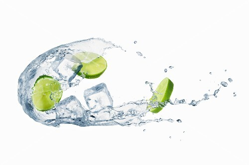 A splash of water with limes and ice cubes