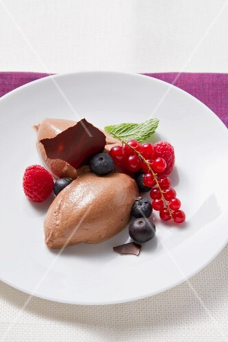 Mousse au chocolat garnished with fresh berries and mint