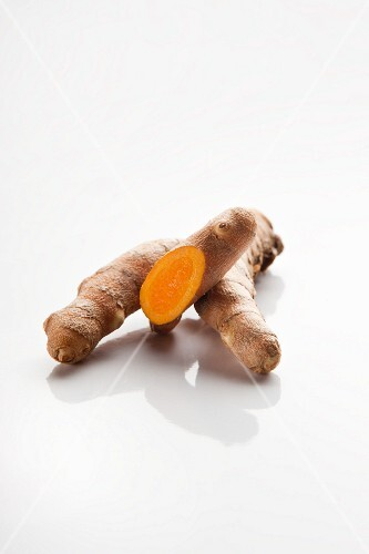 A slice turmeric root on a white surface