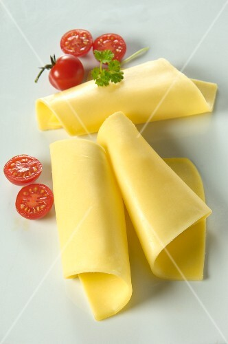 Rolls of cheese with cherry tomatoes and a chervil leaf