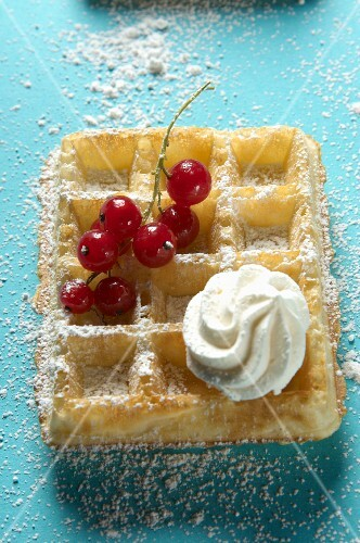 A waffle topped with redcurrants, icing sugar and a dollop of cream