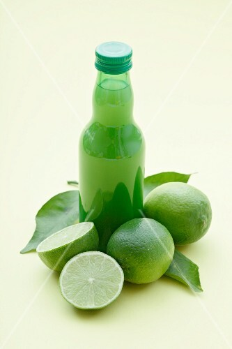 A bottle of lime juice and fresh limes
