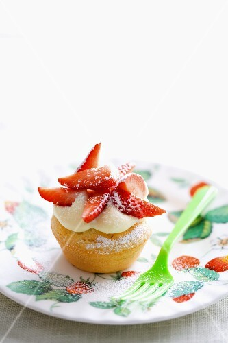 A cupcake topped with white chocolate cream and strawberries