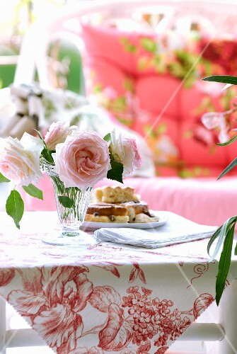 Roses and cakes on small bamboo table