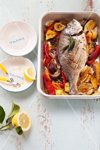 Trout filled with sage on a bed of oven-roasted vegetables