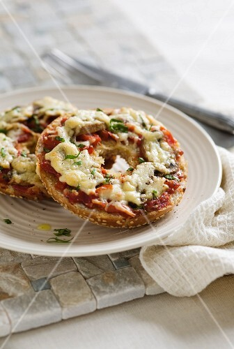 A bagel topped with mushrooms, tomatoes and cheese