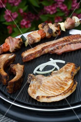 A pork chop, a kebab and a rib on a barbecue