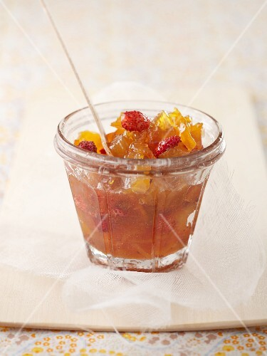 A glass of apricot and strawberry jam