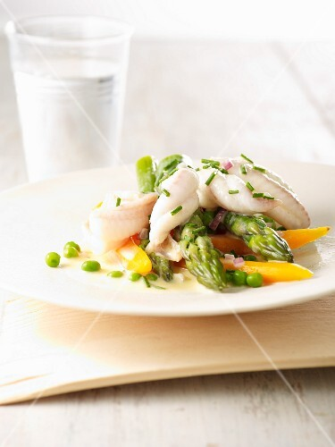 Steamed fish fillet strips on a bed of spring vegetables