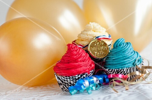 Cupcakes and a medal in front of golden balloons (England)