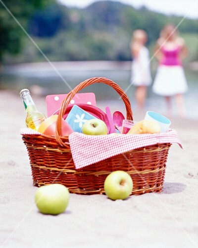 A picnic basket filled with apples, lemonade and baguettes on the beach