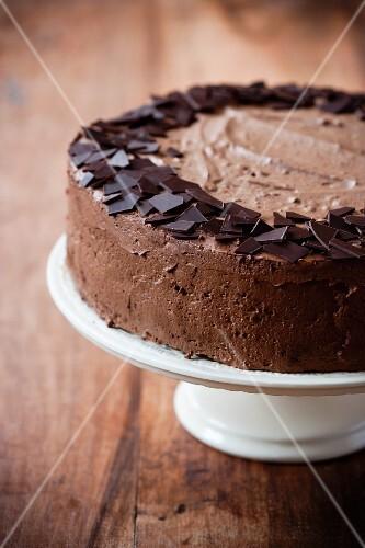 A chocolate cream cake on a cake stand