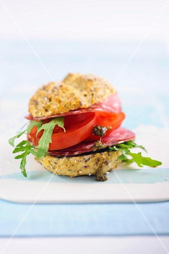 A wholemeal roll filled with salami, tomatoes and rocket