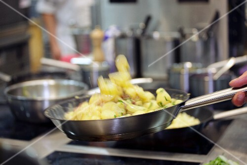 Potatoes being tossed in a pan