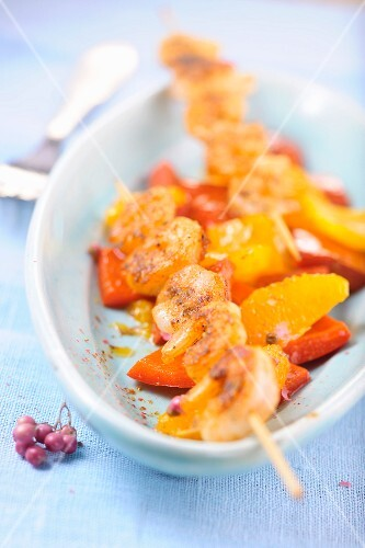 Prawn kebabs on a bed of peppers and fruit