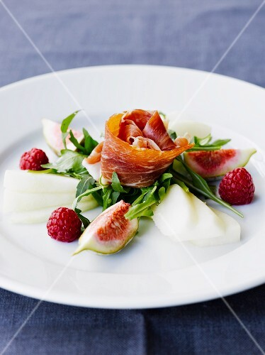 Raw ham with figs, raspberries and rocket