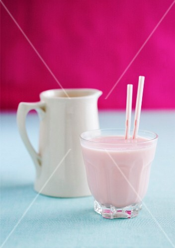 Strawberry milkshake and a milk jug