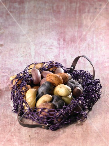Various types of potatoes in a net shopping bag