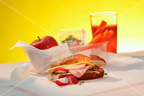 A sandwich, an apple, carrots and a raspberry smoothie with a lunchbox
