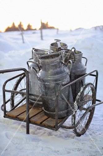 Milk churns on a cart in the snow