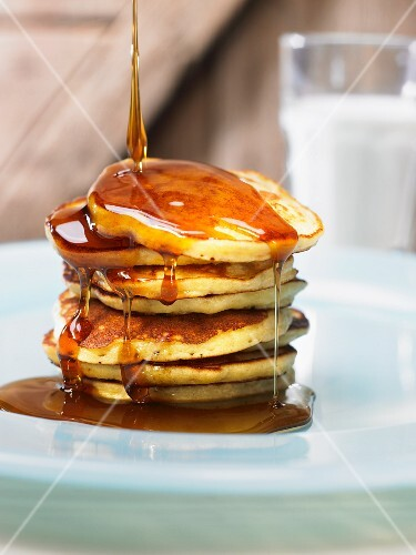 Maple syrup being drizzled over a stack of pancakes