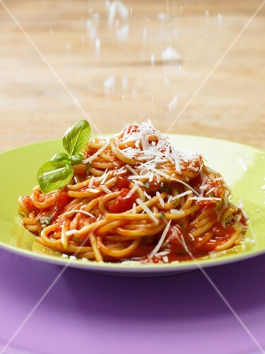 Spaghetti with tomato sauce being sprinkled with Parmesan