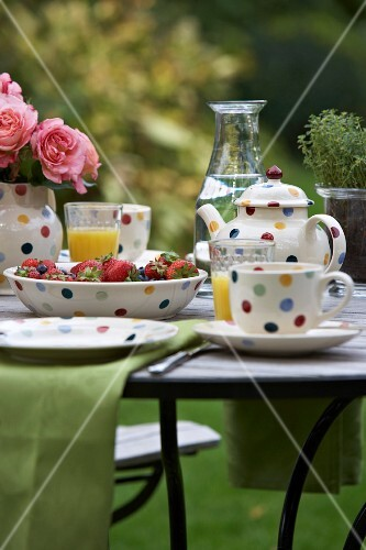 Breakfast laid in a garden with strawberries and orange juice