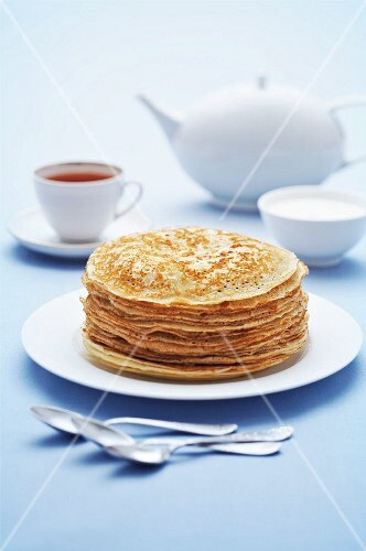 A stack of pancakes, sour cream and tea