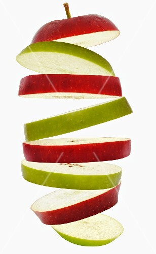 Flying slices of red and green apple