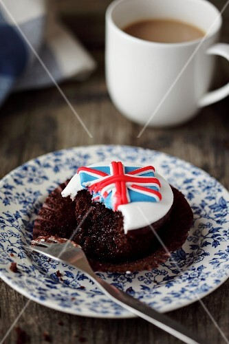 A Union Jack cupcake with a bite take out (Great Britain)