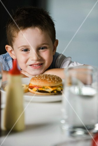 A little boy sitting at a table with a cheeseburger