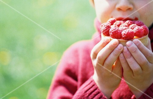 A child eating a raspberry tartlet