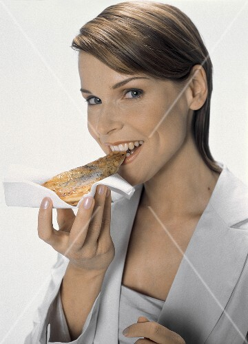 Young woman in white blazer eating a piece of pizza