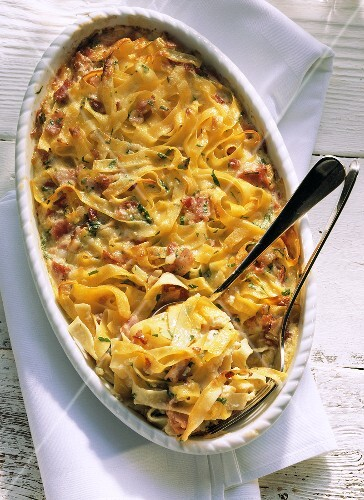 Noodle and ham bake with basil in casserole dish