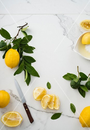 an arrangement of lemons with a sprig and sliced lemons