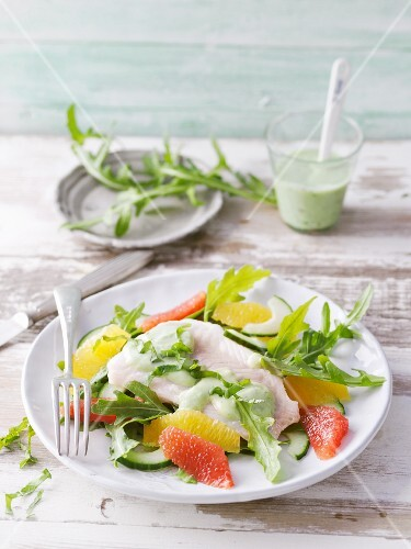 Steamed fish fillet with a cucumber and rocket salad and citrus fruits