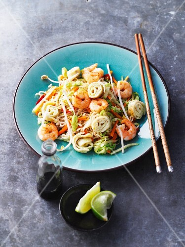 Fried oriental noodles with vegetables, prawns and on roles (Asia)